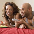 African couple watching television in bed — Stock Photo