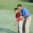 Hispanic father helping son play golf — Stock Photo