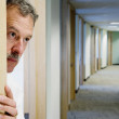 Middle-aged businessman peeking out of office doorway — Stock Photo