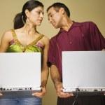 Studio shot of Hispanic couple holding laptops — Stock Photo #23272230