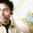 Pacific Islander man wearing headset next to globe — Stock Photo