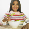 Hispanic girl eating salad — Stock Photo