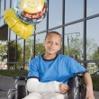 African boy with broken arm and balloons in wheelchair — Stock Photo