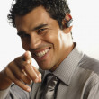 Studio shot of pointing Hispanic businessman with wireless earpiece — Foto de Stock