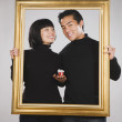 Asian couple holding gift inside picture frame — Stock Photo