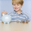 Young boy putting change in piggy bank — Stock Photo