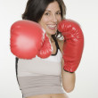 Hispanic woman wearing boxing gloves — Stock Photo