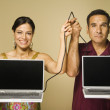 Hispanic couple holding cable connecting two laptops — Stock Photo