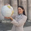 Businesswoman holding globe in front of building — Stock Photo