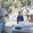 African father and sons washing car in driveway — Stock Photo