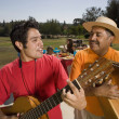 Hispanic father and adult son playing instruments at party — Stock Photo