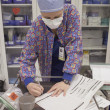 Nurse with surgical mask writing in chart — Stock Photo