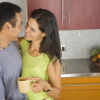 Hispanic couple hugging in kitchen — Stock Photo