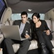 Hispanic businesspeople working in limousine — Stock Photo