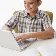 Hispanic boy doing homework on laptop — Stock Photo