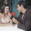 Hispanic man giving girlfriend flower at outdoor cafe — Stock Photo #23272574