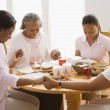 African family holding hands and praying at dinner table — Stock Photo
