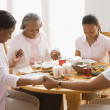African family holding hands and praying at dinner table — Stock Photo #23272580