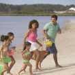 Hispanic family running on beach — Stock Photo