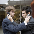 Hispanic businessmen holding cell phones up to each other's ears — 图库照片