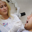 Female dentist examining patient — Stock Photo