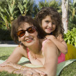 Hispanic grandmother and granddaughter laying on grass — Stock Photo