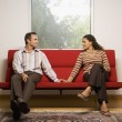 Couple smiling at each other on sofa — Stock Photo