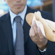 Businessman eating hot dog outdoors — Stock Photo