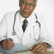 Portrait of Indian male doctor writing on chart — Stock Photo