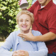 Hispanic man putting party hat on mother — Stock Photo