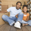 African father and daughter smiling in back of moving truck — Stock Photo