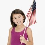 Studio shot of Asian girl holding American flag — Stock Photo