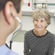 Senior woman talking to doctor in hospital — ストック写真
