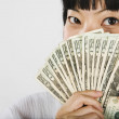 Asian woman holding money in front of face — Stock Photo