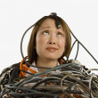 Studio shot of Asian woman buried in computer cables — Stock Photo