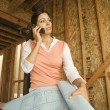 Hispanic woman talking on cell phone at construction site — Foto Stock