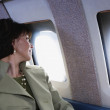 Businesswoman looking out widow on private airplane — Stock Photo