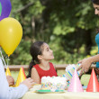 Hispanic girl receiving gift at birthday party in park — Stock Photo