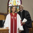 African American female and male Reverends in church - Stock Photo