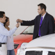 Hispanic couple taking keys from car salesman — Stock Photo