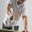 Hispanic man sawing wood board — Stock Photo