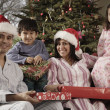 Hispanic family holding Christmas gifts — Stock Photo