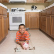 Hispanic boy with piggybank on floor — Stockfoto