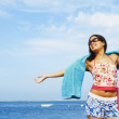 Hispanic woman with arms outstretched at beach — Stockfoto