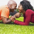 African couple laughing in grass — Stock Photo