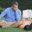 Hispanic couple relaxing in grass — Stock Photo