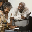 Senior African woman playing piano — Stock Photo