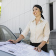 Eurasian businesswoman spreading blueprints on car — Stock Photo