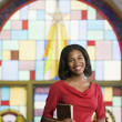 African American woman with Bible in church - Stock fotografie