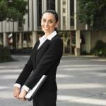 Hispanic businesswoman holding laptop outdoors — Stock Photo #23275678
